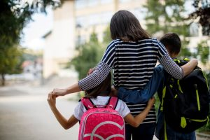 Mother walking two children to school